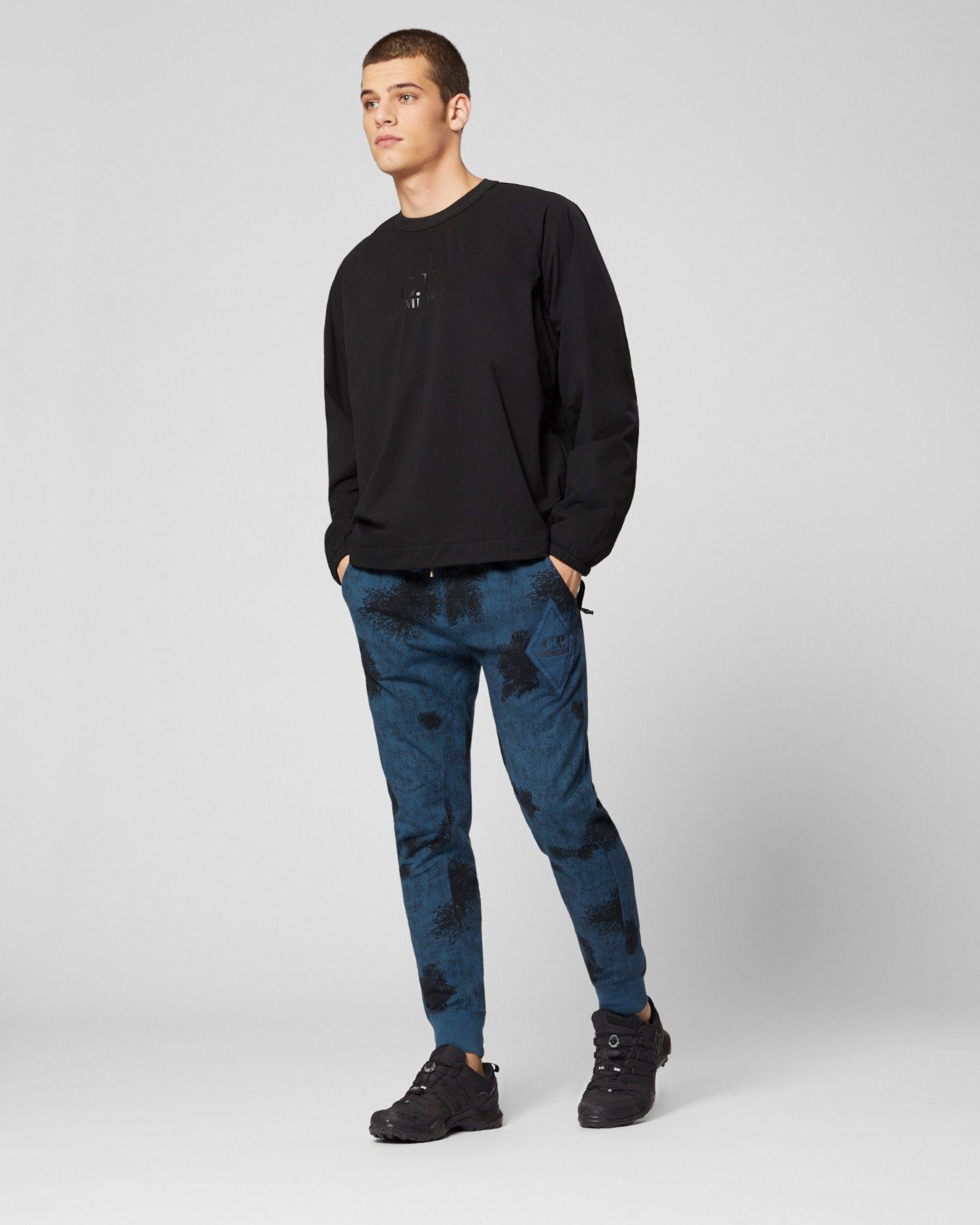 Pantalones de deporte teñidos en prenda de tejido polar de camuflaje con parche