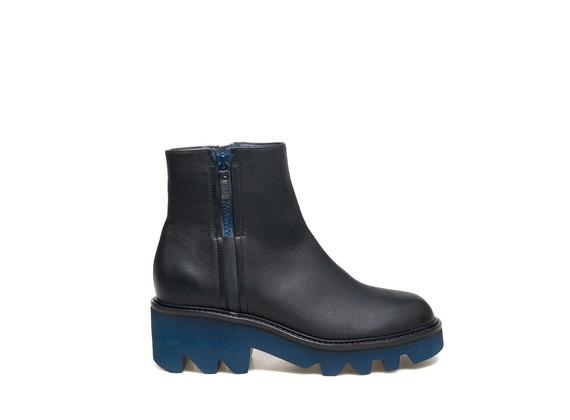 Stiefelette aus schwarzem Leder mit Reißverschluss und grober Sohle aus blauem Gummi