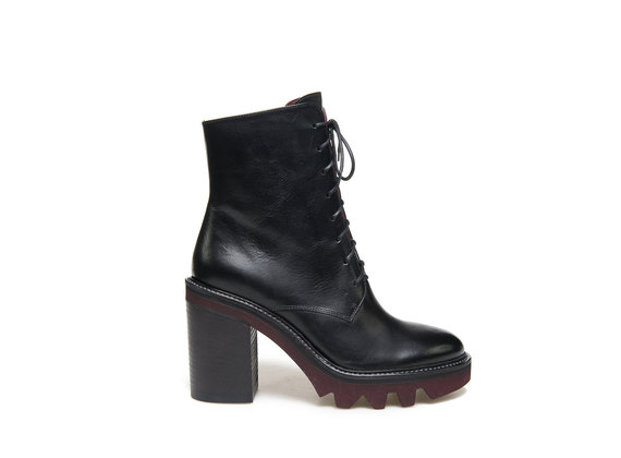 Black military boot with a contrasting rubber lug sole with heel