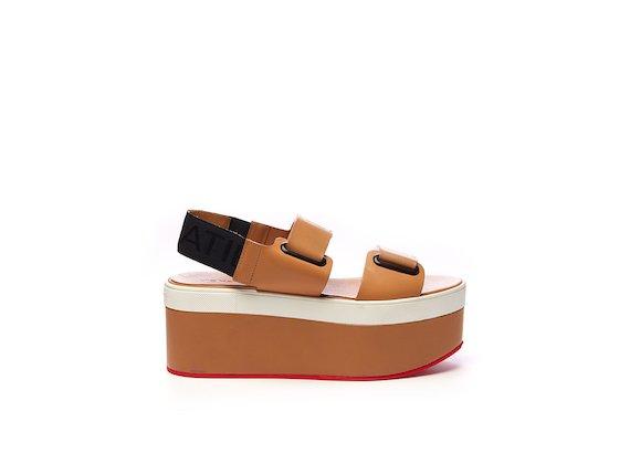 Lederfarbene Sandale mit Ösen, Klettverschlüssen und Flatform-Sohle.