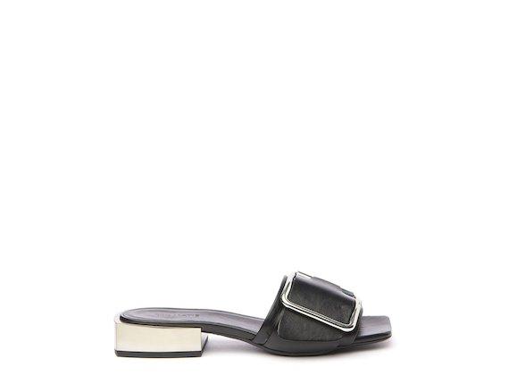 Black flat sandal with metal heel and buckle