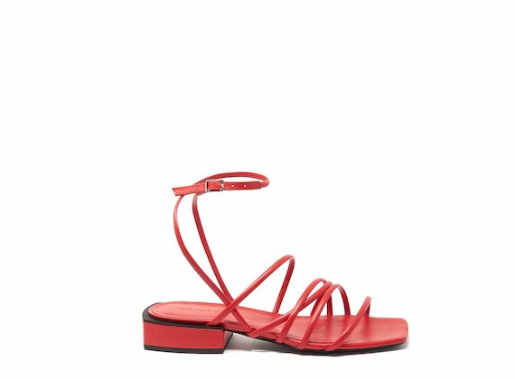 Flat red sandals with strips and ankle strap